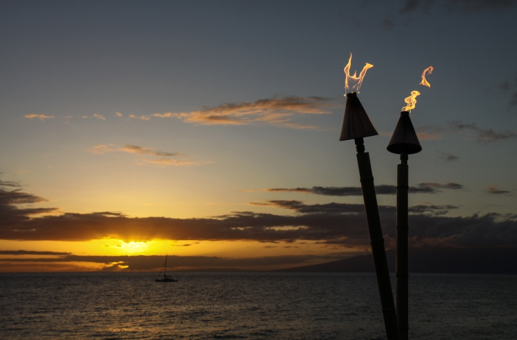 Tiki torches adding a Hawaiian dimple to the lovely smile of the setting Sun